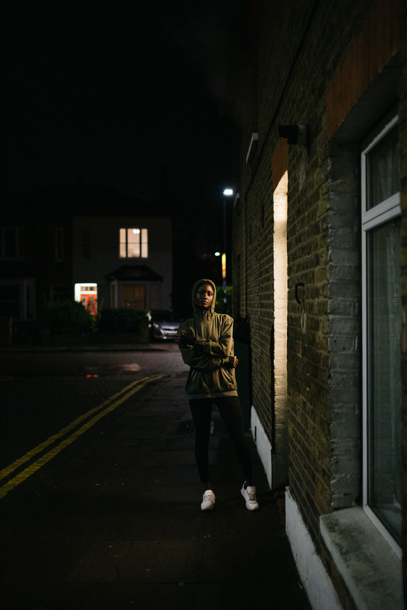 Young ethnic woman on street at night