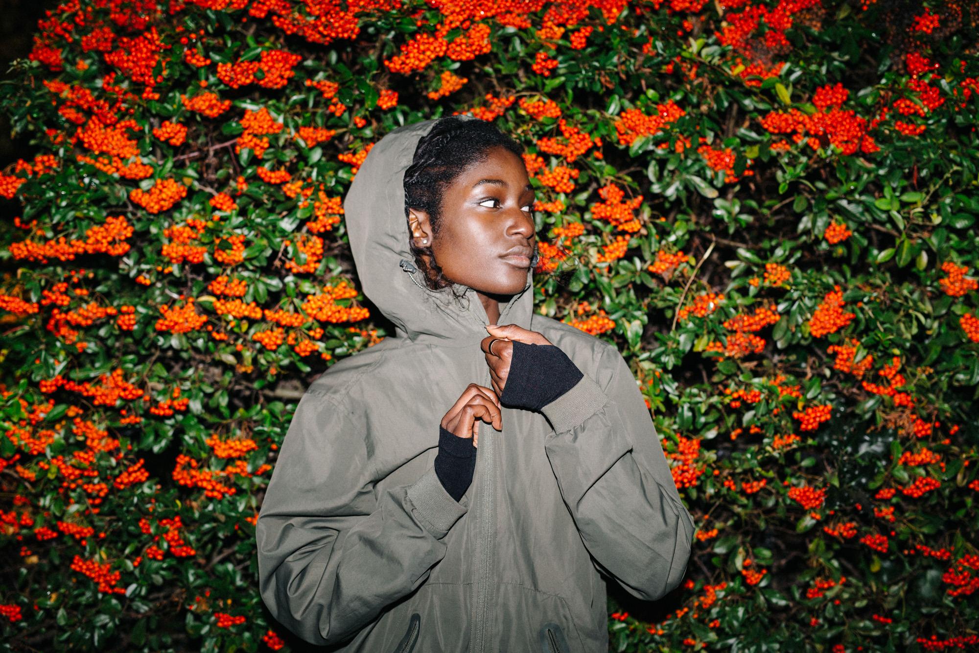 Woman zipping jacket at bush