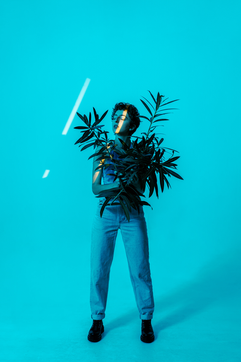 Androgynous model with bunch of leaves