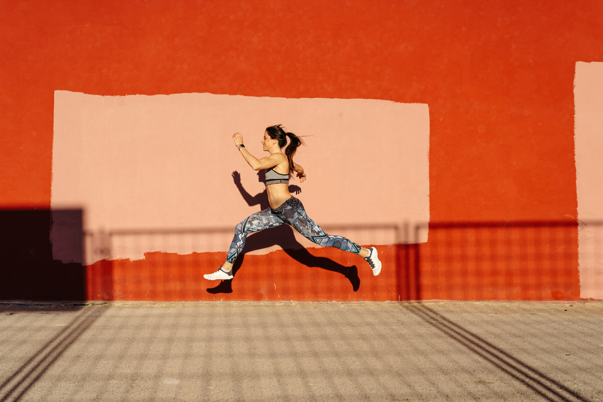 Slim sportswoman leaping against weathered wall