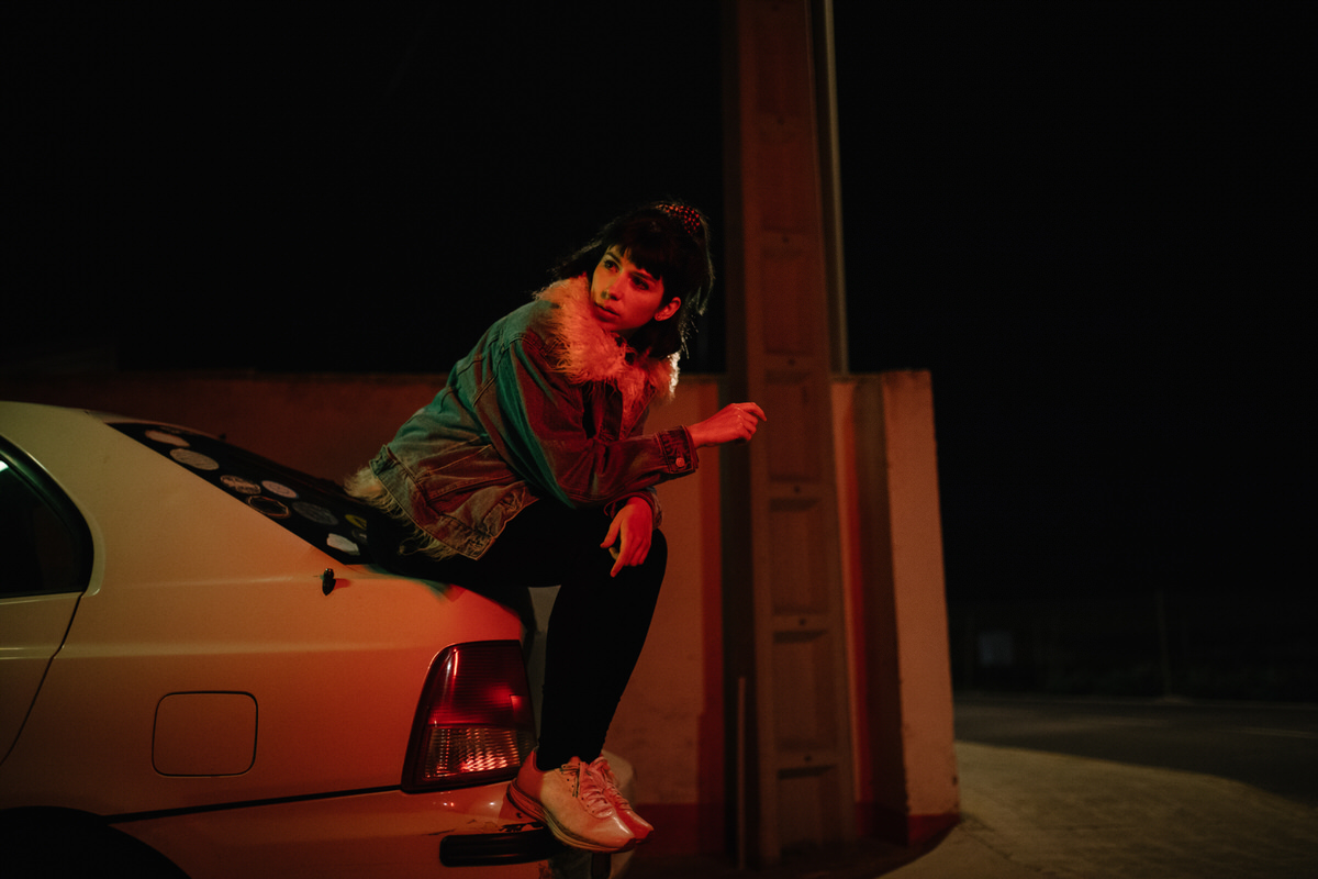 Confident model on car trunk in night