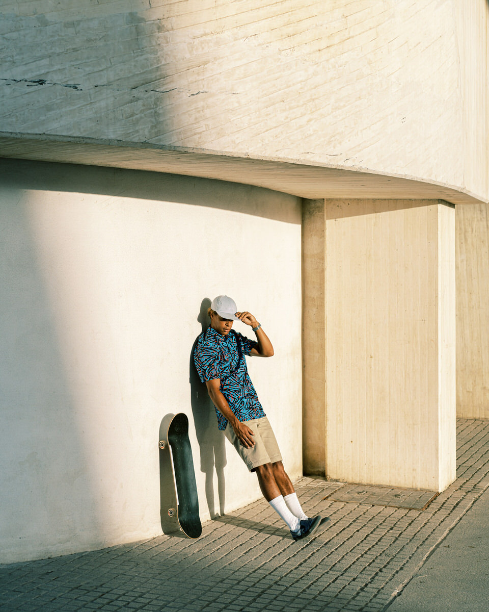 Ethnic man with skateboard outside modern building