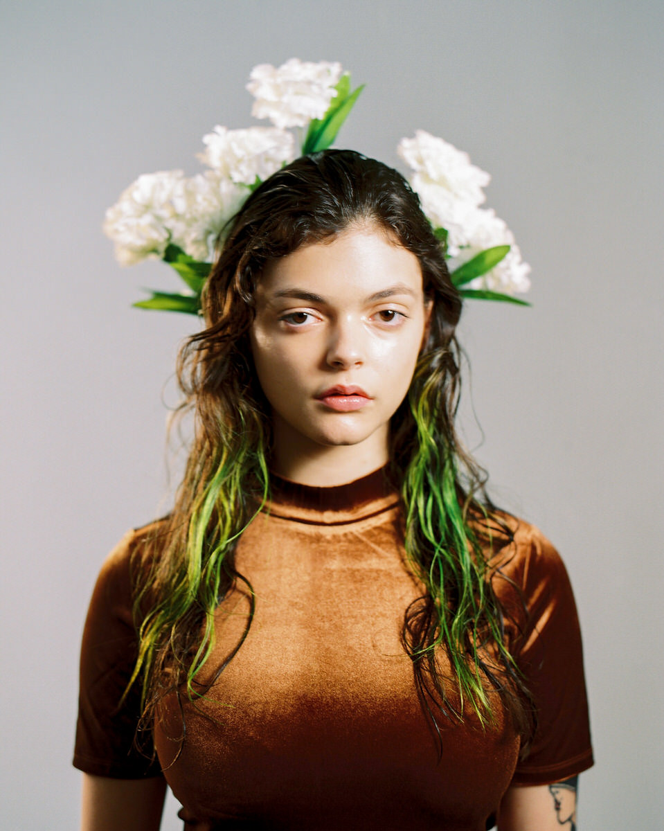 Gorgeous young model with flowers behind head