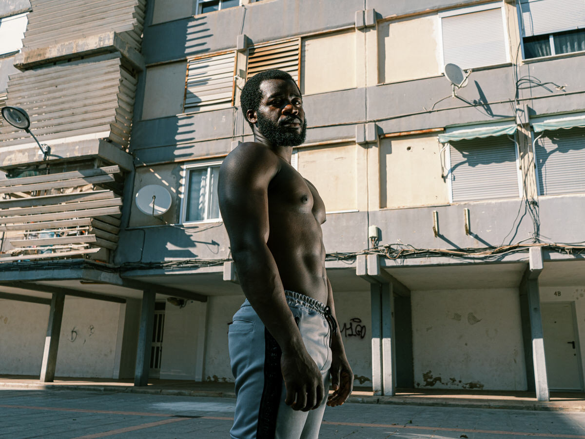 Muscular black sportsman standing on sports ground