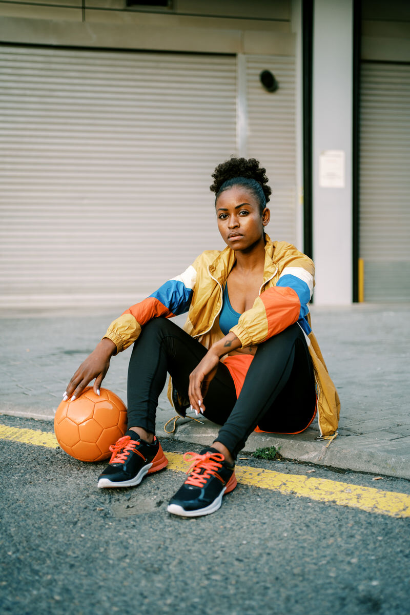 Female footballer with ball in city