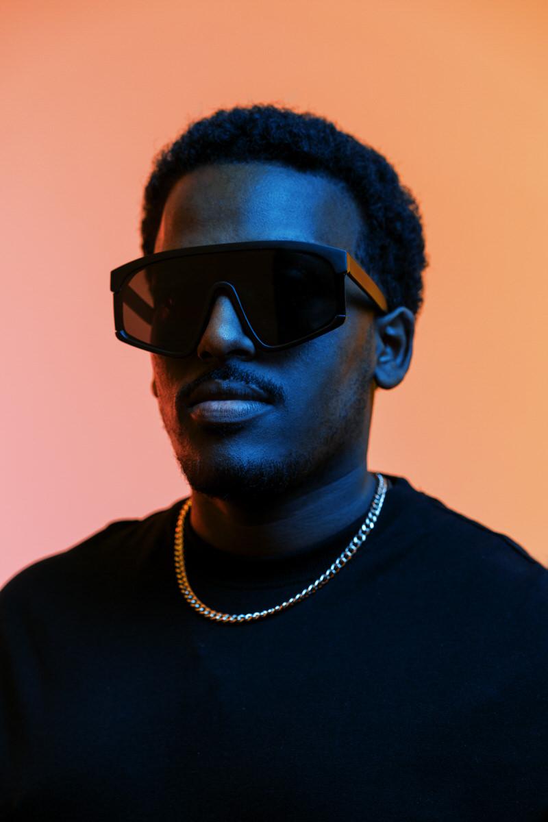 Stylish black man in sunglasses in studio