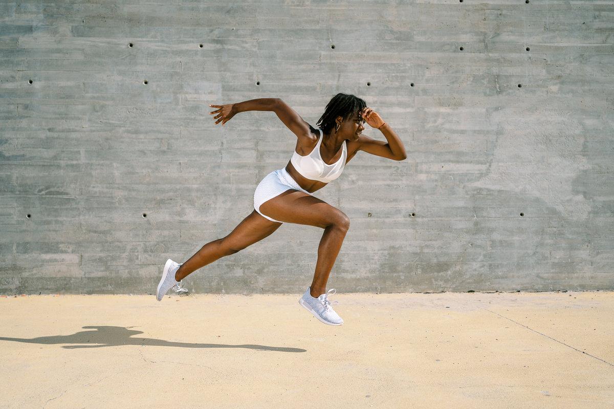 Energetic black sportswoman running in city
