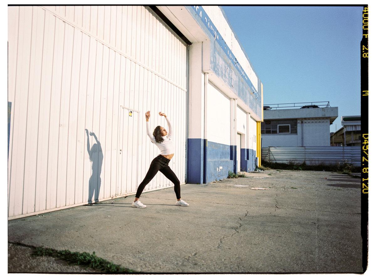 Slim sportswoman warming up on street during training