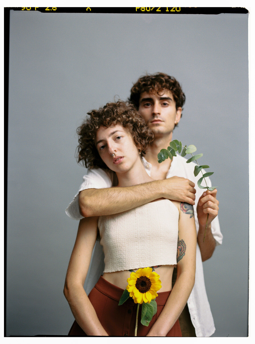 Tender couple with flower in studio