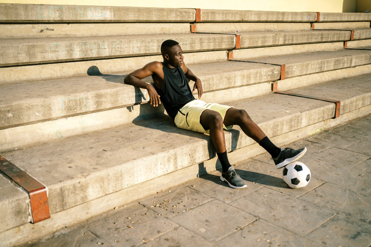 Black football player resting during training
