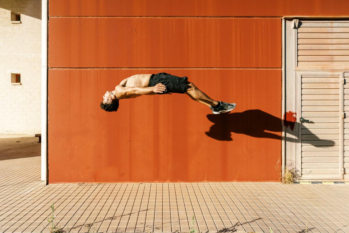 Agile sportsman doing back jump trick on street